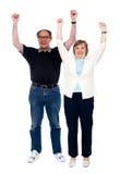 Pares envejecidos emocionados que presentan con los brazos levantados imágenes de archivo libres de regalías
