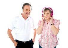 Pares envejecidos felices que disfrutan de la música junta fotos de archivo