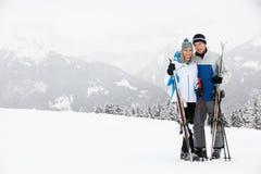 Pares envejecidos medios el día de fiesta del esquí en montañas Fotografía de archivo libre de regalías