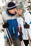 Pares envejecidos medios el día de fiesta del esquí en montañas Foto de archivo