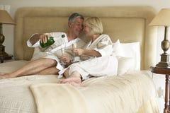 Pares envejecidos medios que disfrutan de Champán en dormitorio Imagenes de archivo