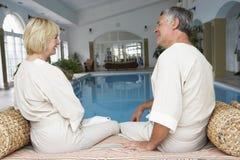 Pares envejecidos medios que se relajan por la piscina Foto de archivo libre de regalías