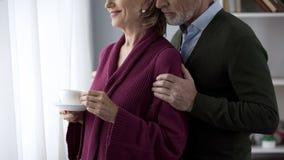 Pares envejecidos que miran en la señora de la ventana que sostiene la taza de té, hombre que la abraza detrás imagen de archivo libre de regalías