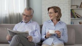 Pares envejecidos que se sientan en el sofá, periódico de la lectura del hombre, mujer que goza del té, anuncio almacen de metraje de vídeo