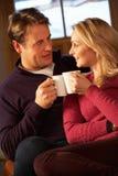 Pares envelhecidos médios que sentam-se no sofá com bebidas quentes Foto de Stock Royalty Free