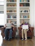 Pares envelhecidos meio com jornal e portátil em casa fotos de stock royalty free