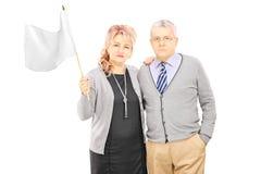 Pares envelhecidos meio que acenam uma bandeira branca fotografia de stock