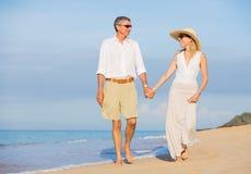 Pares envelhecidos meio que apreciam a caminhada na praia Foto de Stock