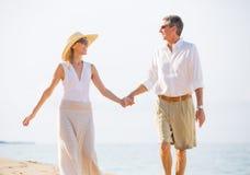 Pares envelhecidos meio que apreciam a caminhada na praia Fotos de Stock Royalty Free