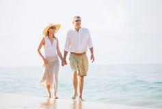 Pares envelhecidos meio que apreciam a caminhada na praia Imagens de Stock Royalty Free