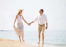 Pares envelhecidos meio que apreciam a caminhada na praia imagem de stock