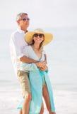Pares envelhecidos meio que apreciam a caminhada na praia Imagem de Stock Royalty Free