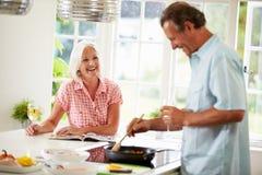 Pares envelhecidos meio que cozinham a refeição na cozinha junto Fotos de Stock Royalty Free