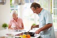 Pares envelhecidos meio que cozinham a refeição na cozinha junto Imagem de Stock
