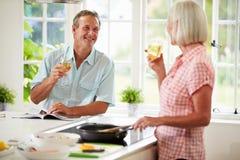 Pares envelhecidos meio que cozinham a refeição na cozinha junto Fotografia de Stock