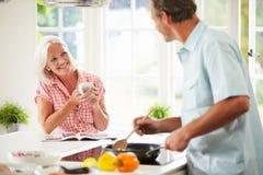 Pares envelhecidos meio que cozinham a refeição na cozinha junto foto de stock