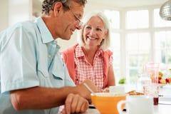 Pares envelhecidos meio que olham a tabuleta de Digitas sobre o café da manhã Fotos de Stock