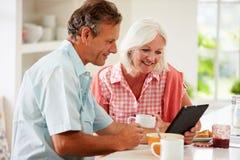 Pares envelhecidos meio que olham a tabuleta de Digitas sobre o café da manhã Imagens de Stock Royalty Free