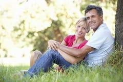Pares envelhecidos meio que relaxam no campo que inclina-se contra a árvore Imagens de Stock Royalty Free