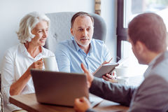 Pares envelhecidos positivo que consultam com o agente de seguros fotografia de stock royalty free