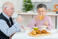 Pares envelhecidos que têm o divertimento na cozinha no tempo de café da manhã imagem de stock