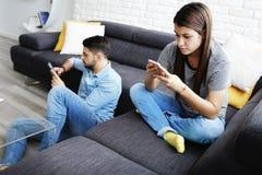 Pares enviciados a las redes sociales usando los teléfonos Fotos de archivo