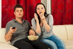 Pares espantados que prestam atenção à tevê Foto de Stock Royalty Free