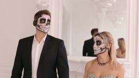 Pares espeluznantes con el maquillaje asustadizo de Halloween en trajes del vintage en un estudio almacen de video
