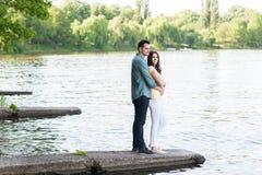 Pares espontâneos no amor, abraçado, em um cais de pedra Imagem de Stock Royalty Free