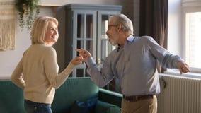 Pares, esposa feliz y marido envejecidos medios bailando en casa imagenes de archivo
