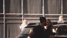 Pares europeos jovenes cruzar la calle junto El individuo con el funcionamiento de la guitarra y de la muchacha que lleva a cabo  almacen de video