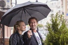 Pares europeus que andam sob o guarda-chuva no dia do outono Imagens de Stock