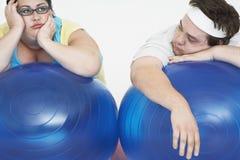 Pares excessos de peso cansados que descansam em bolas do exercício Foto de Stock