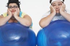 Pares excessos de peso cansados que descansam em bolas do exercício Fotos de Stock Royalty Free