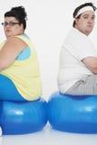 Pares excessos de peso infelizes que sentam-se em bolas do exercício Imagens de Stock