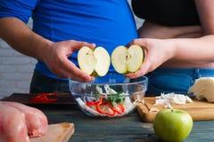 Pares excessos de peso que cozinham o alimento da dieta O homem e a mulher gordos comem a maçã Fotos de Stock Royalty Free