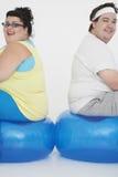 Pares excessos de peso que sentam-se em bolas do exercício Imagens de Stock