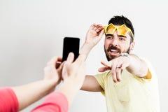Pares excitados que tomam fotografias e selfies móveis fotografia de stock royalty free