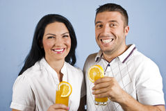 Pares extremadamente felices con el zumo de naranja Fotografía de archivo libre de regalías