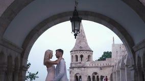 Pares fabulosos en el amor que abraza suavemente en el castillo magnífico en Budapest, Hungría Concepto de la luna de miel almacen de metraje de vídeo