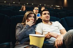 Pares fascinados mirando la película en cine Imagen de archivo libre de regalías