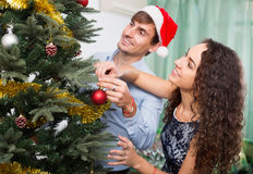 Pares felices adultos que adornan el árbol de navidad Fotografía de archivo libre de regalías