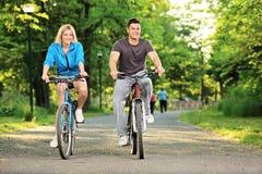 Pares felices biking en el parque Imagen de archivo libre de regalías