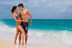 Pares felices cariñosos jovenes en la playa tropical Fotos de archivo libres de regalías