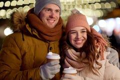 Pares felices con café sobre luces de la Navidad Fotografía de archivo libre de regalías