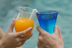 Pares felices con dos vidrios de zumo de naranja Fotografía de archivo