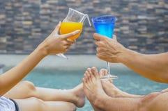 Pares felices con dos vidrios de zumo de naranja Fotografía de archivo libre de regalías