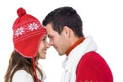 Pares felices con el abarcamiento de la ropa del invierno comparativo Foto de archivo