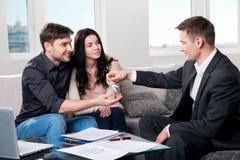 Pares felices con el agente inmobiliario Imágenes de archivo libres de regalías