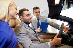 Pares felices con el concesionario de coches en salón del automóvil o salón Imagen de archivo